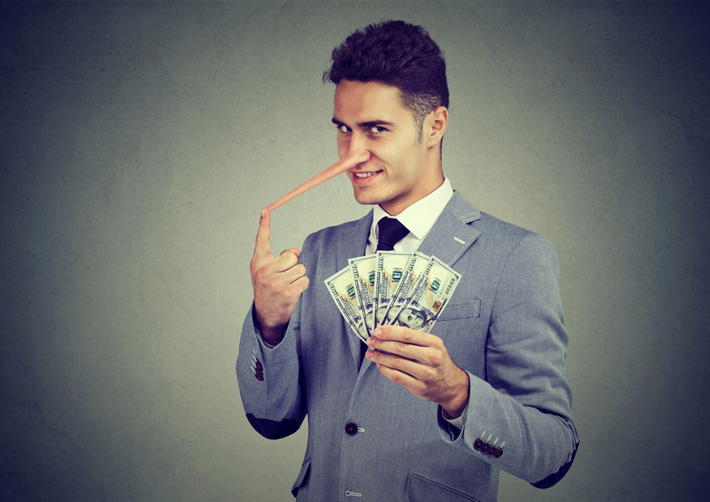 Financial fraud concept. Liar young business man with dollar cash